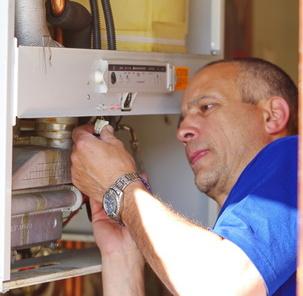 Un artisan vérifie une chaudière à condensation