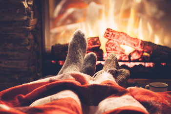 Des jambes avec des chaussettes et un plaid devant les flammes d'une cheminée
