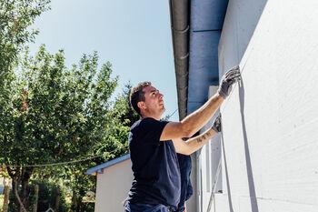 Artisan pose un bloc d'isolant sur un mur extérieur