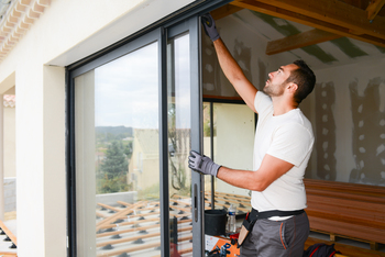 Un artisan pose une baie vitrée