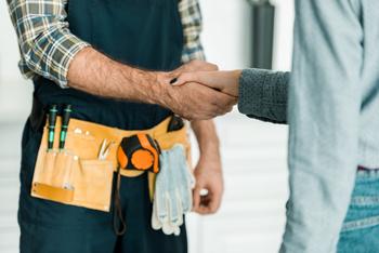 Artisan et particulier se serrant la main